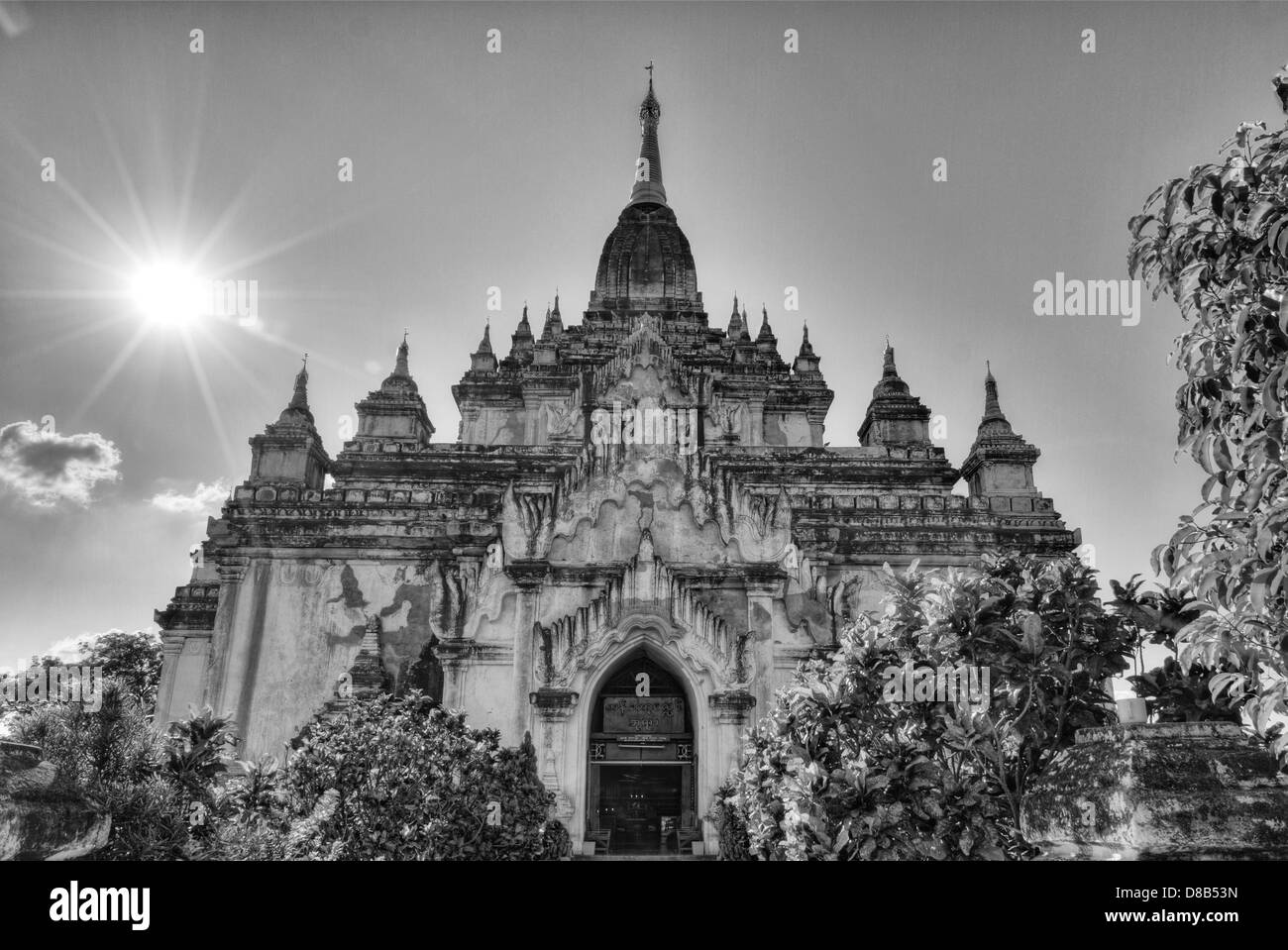 Gold tipped Ananda temple surrounded by bushes with sun in Bagan, Burma - Stock Image