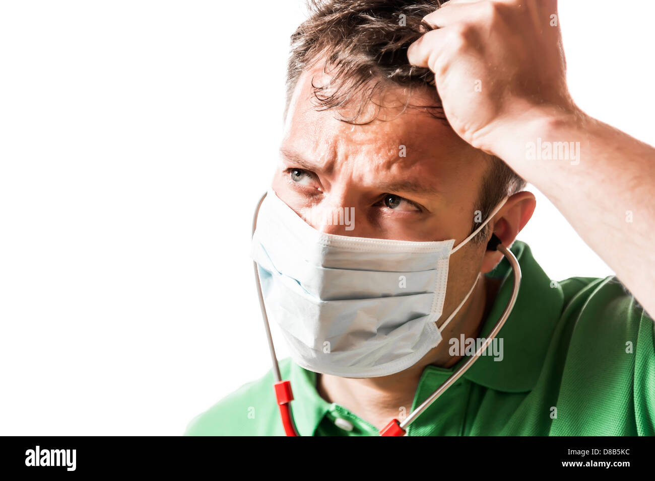 Helpless, anxious and perspiring doctor in a green shirt with a red stethoscope and surgical mask - Stock Image