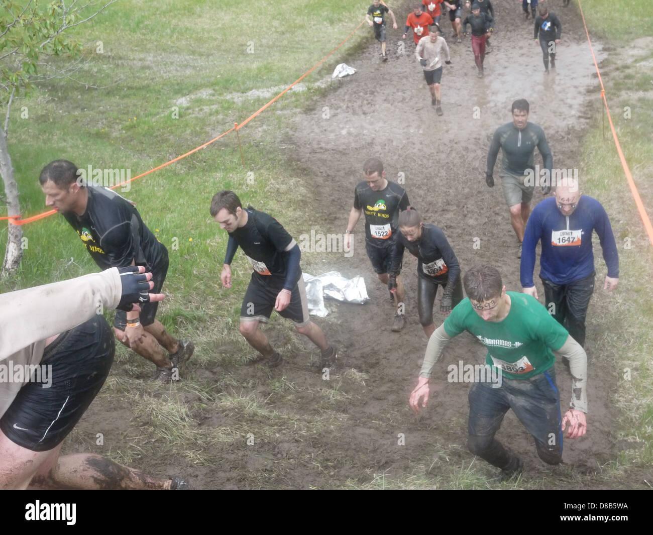 tough mudder people walking on mud - Stock Image