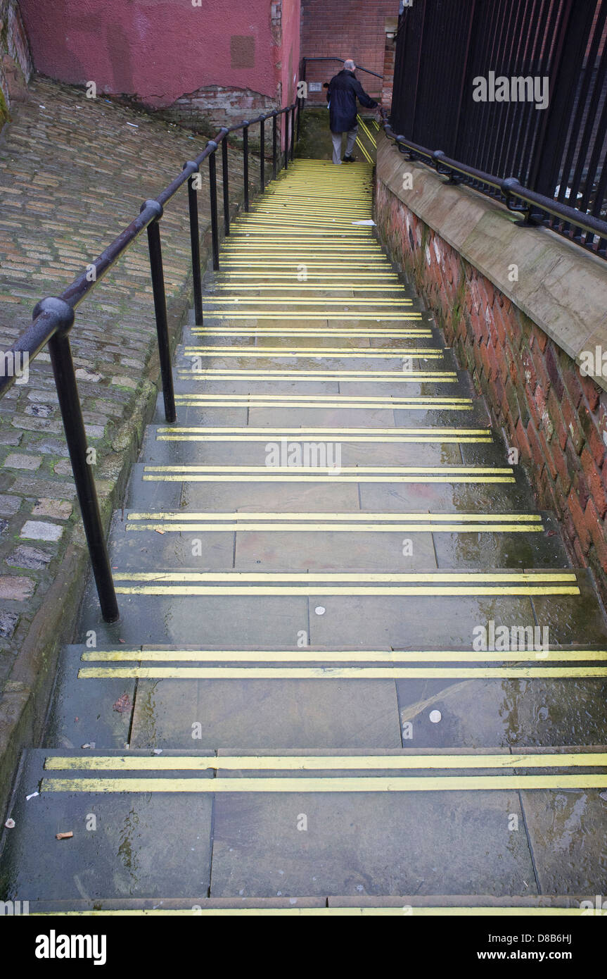 An old man walks down wet steps in Stockport, England - Stock Image