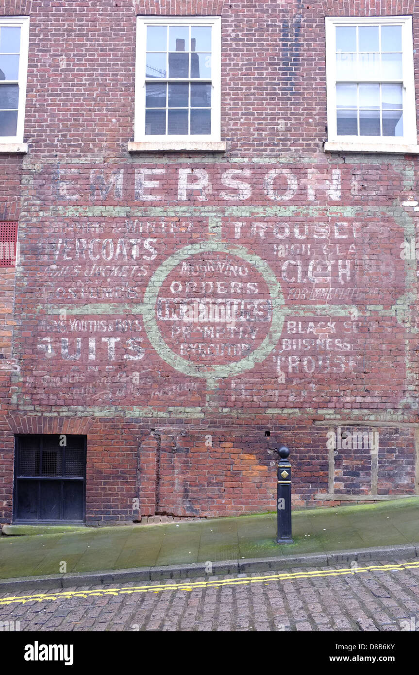 The painted wall of an old shop front in Stockport town centre. - Stock Image