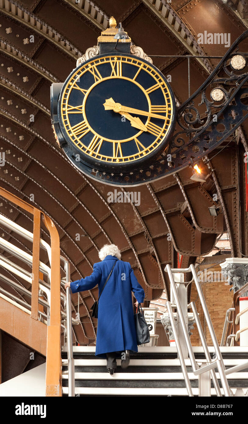 An old woman under the clock at York railway station - concept of time old age elderly running out of time - Stock Image