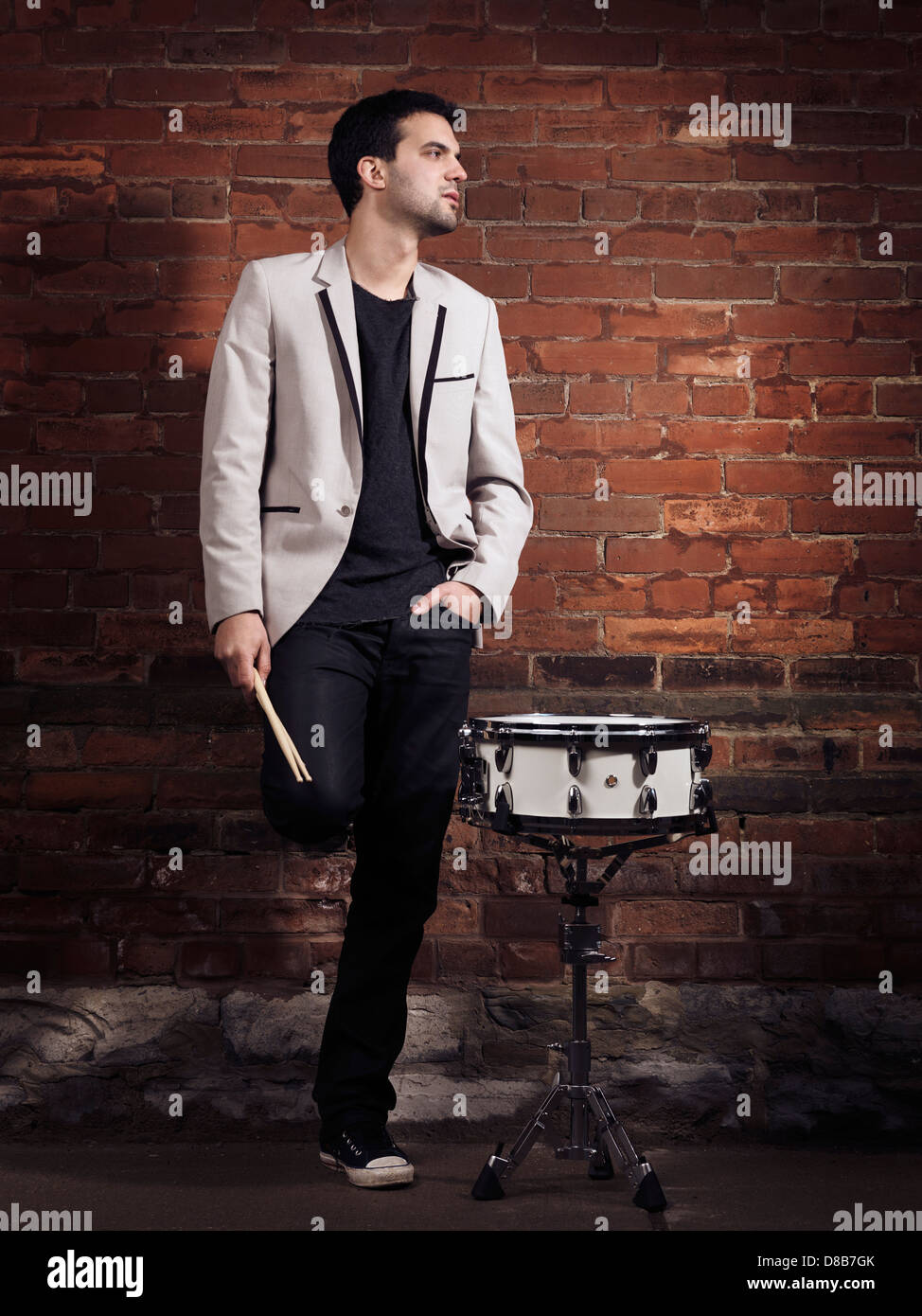 Dramatic portrait of a young man drummer with a snare drum and drumsticks standing at a brick wall - Stock Image