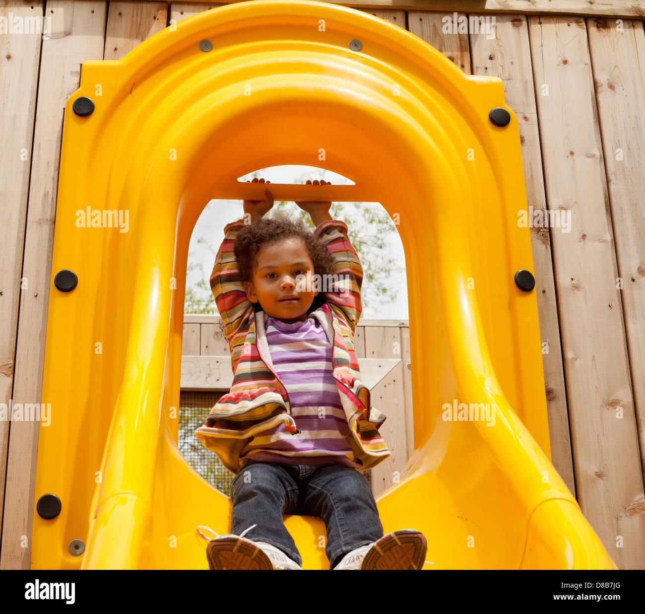 multi racial little girl on a slide - Stock Image