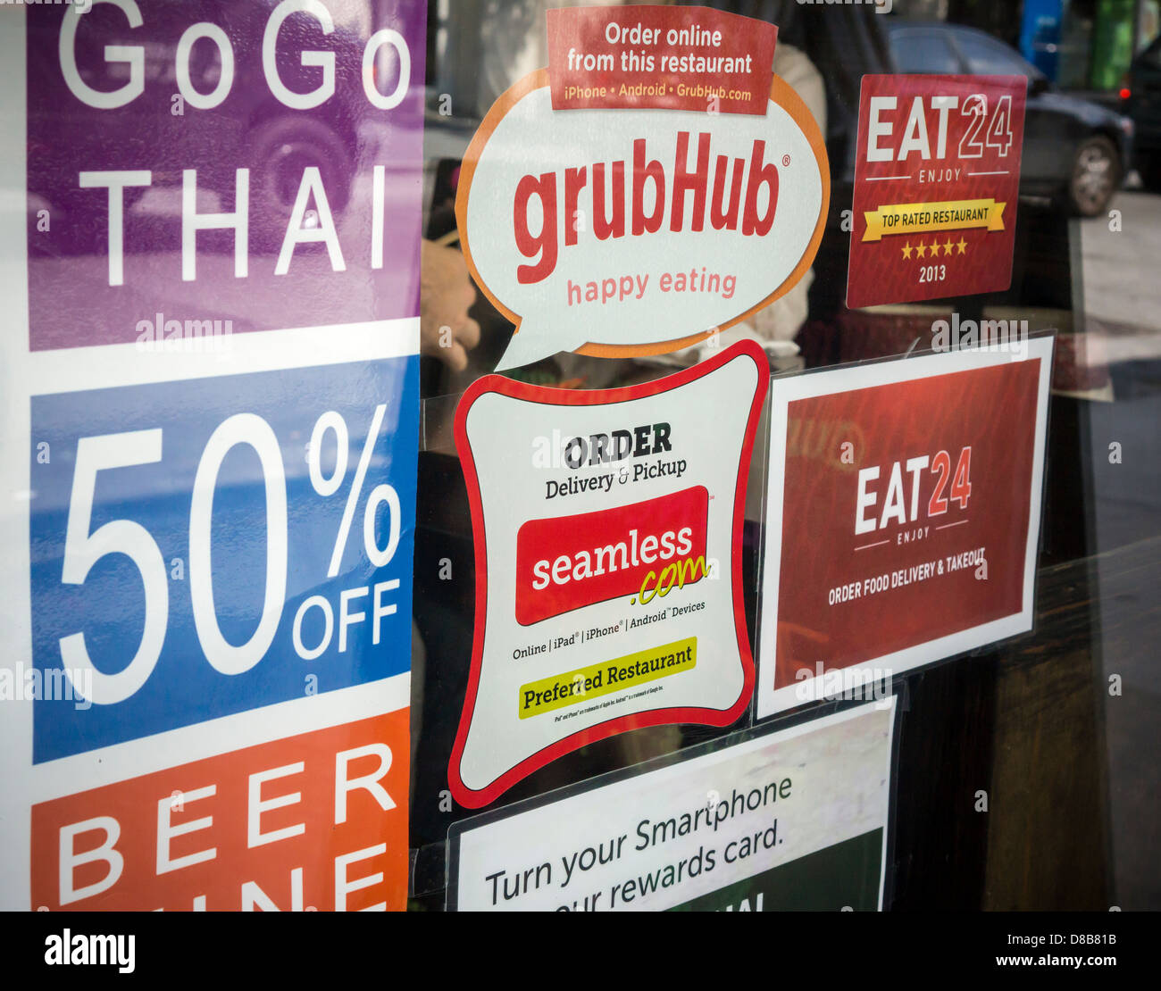 Stickers for seamless and grubhub internet food delivery services are seen on the window of a restaurant in chelsea in new york