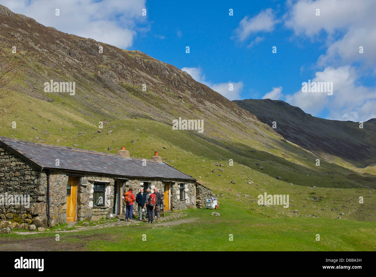 Four walkers standing outside the Black Sail Hut, in Ennerdale, Lake District National Park, Cumbria, England UK - Stock Image