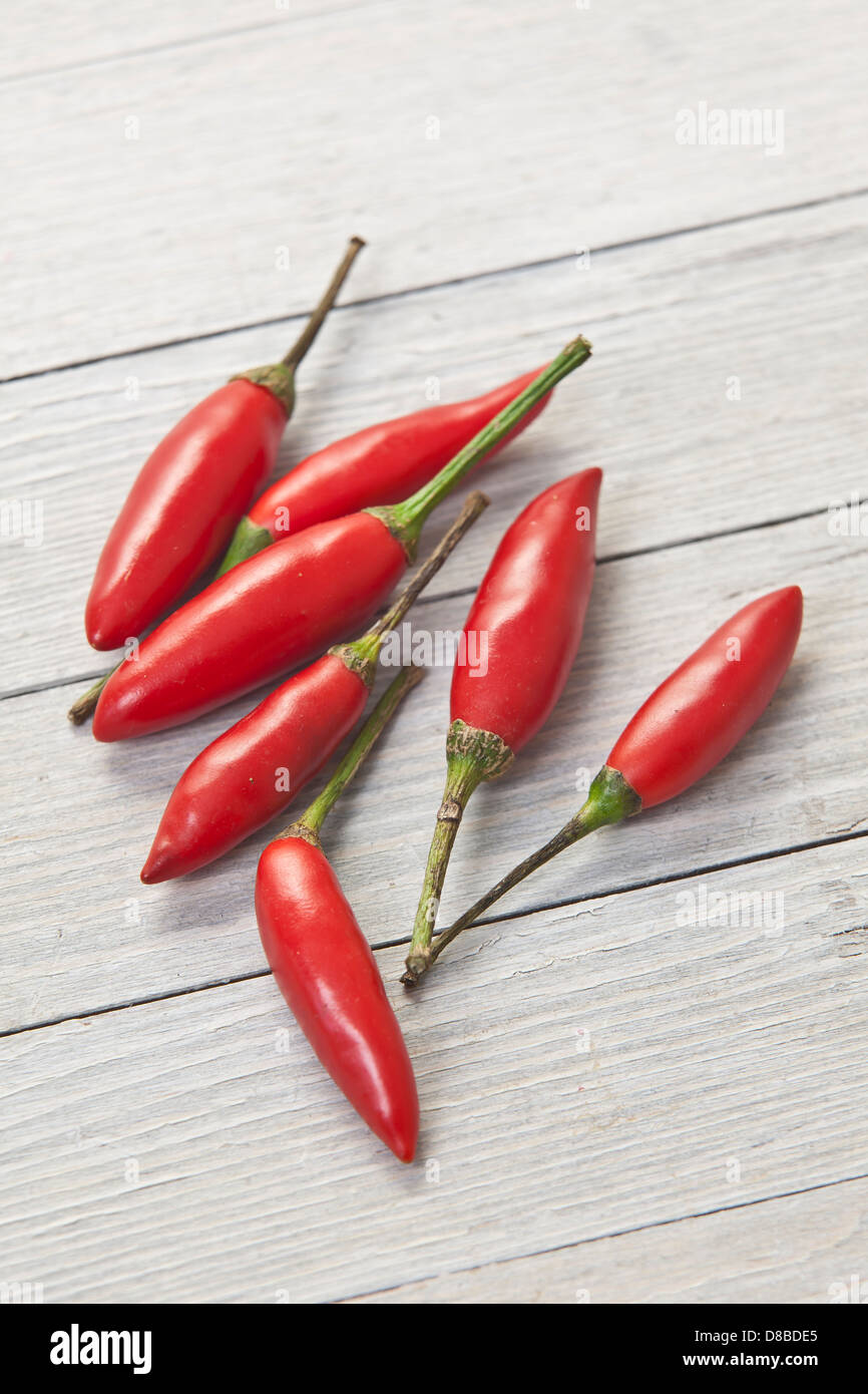Seven red Thai chillies on a rustic wood surface. - Stock Image