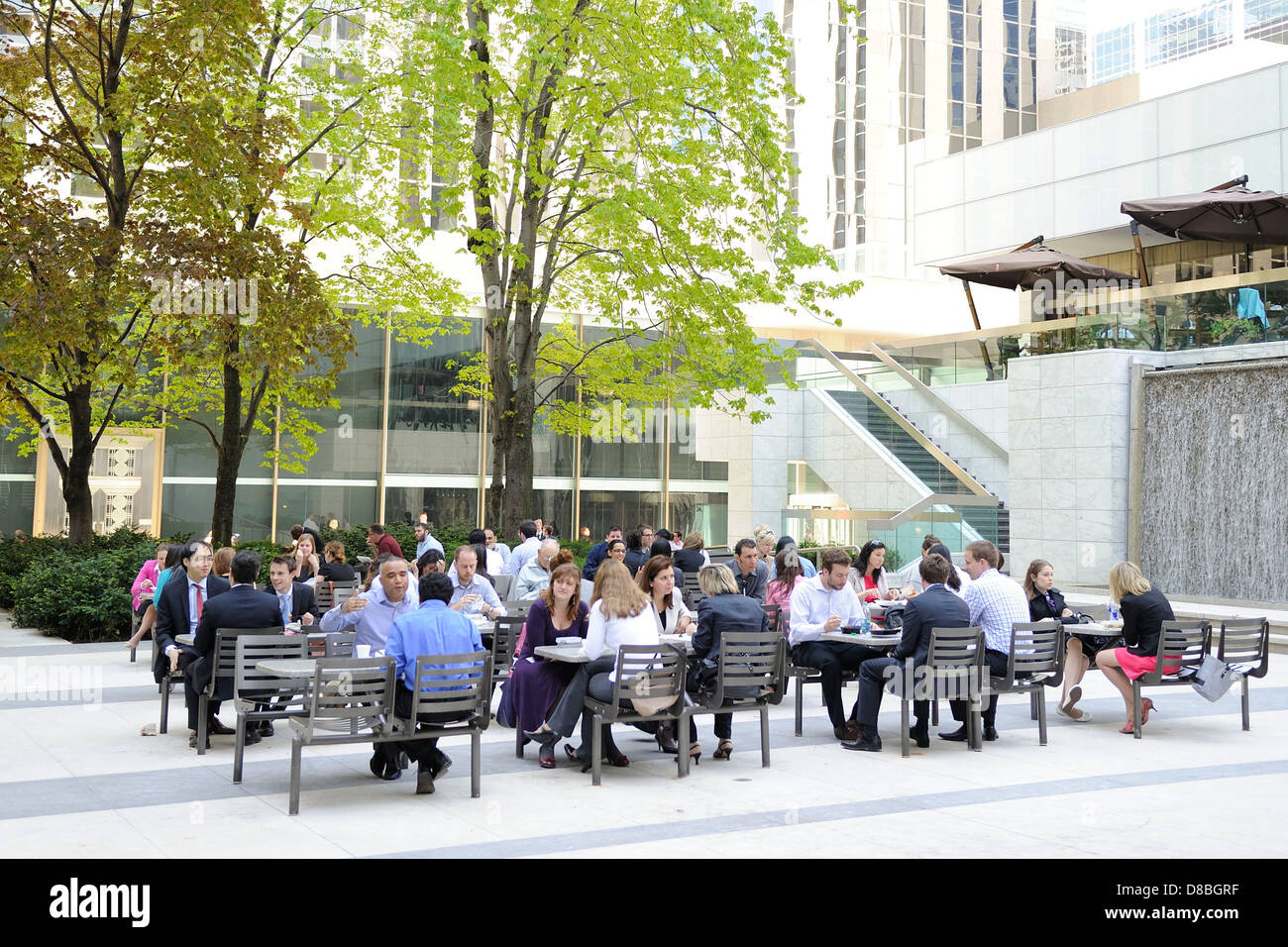 Office Workers Taking Lunch Break At An Outdoor Park Setup With Tables And  Chairs Resembling A