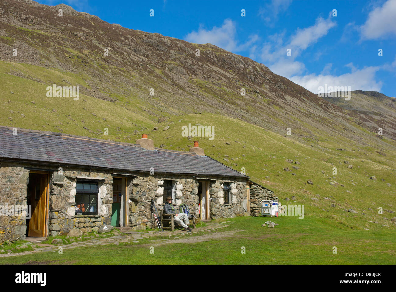 Senior male walker sitting outside the Black Sail Hut, in Ennerdale, Lake District National Park, Cumbria, England - Stock Image