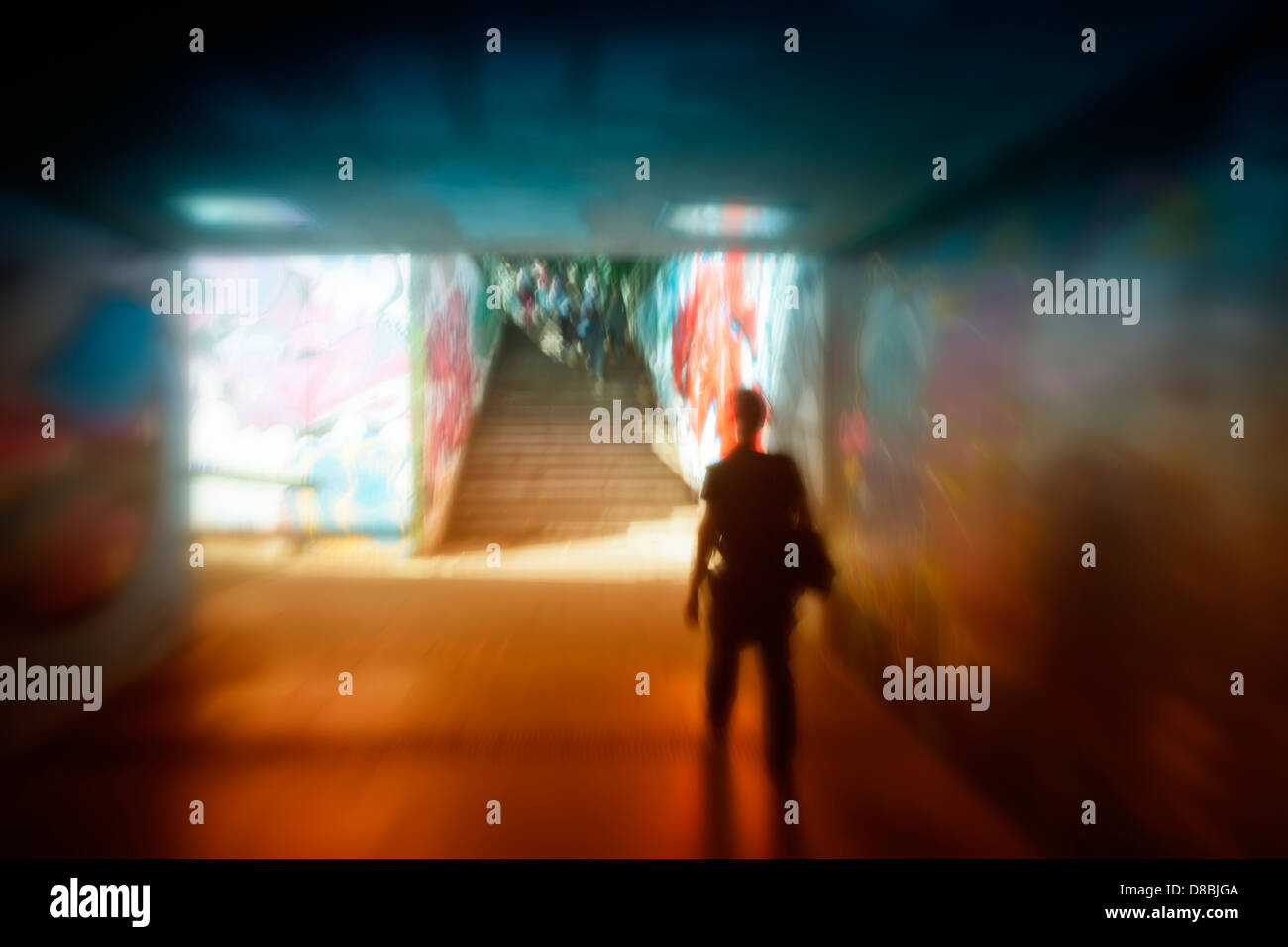 A man walking in a dark tunnel with graffiti, symbolic image for panic, Trier, Rhineland-Palatinate, Germany, Europe - Stock Image