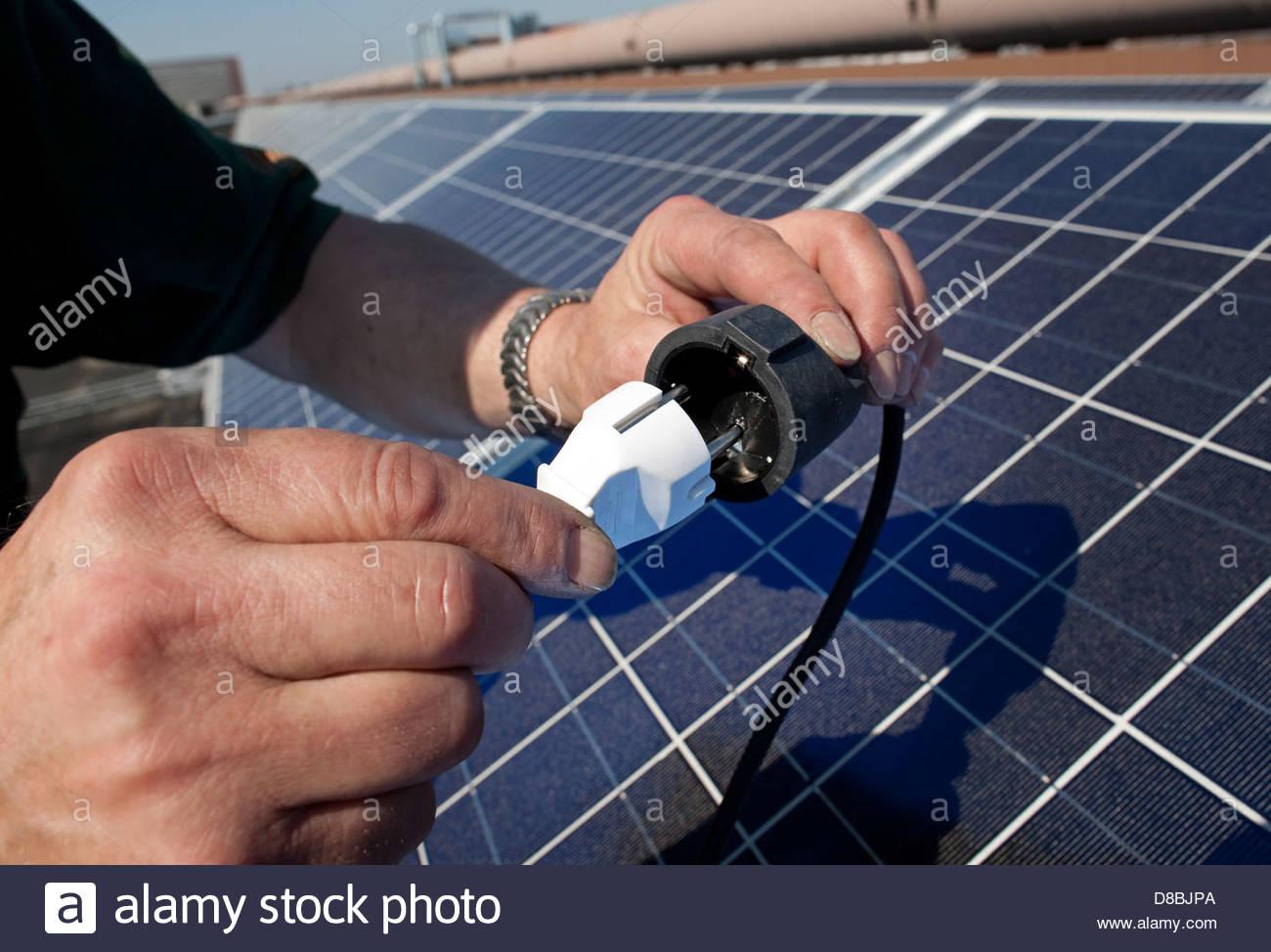 Technician connecting electric plugs near solar panel - Stock Image