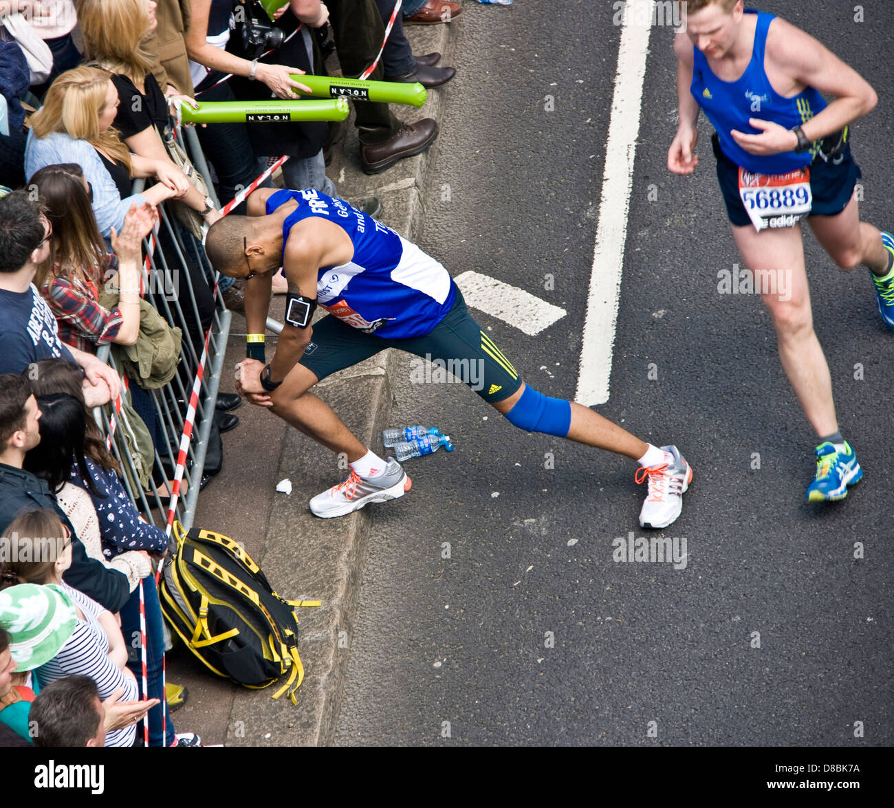 Runner athlete competitor stopping to stretch legs during 2013 London marathon England Europe - Stock Image