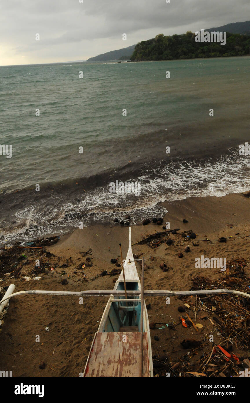 A fishermen boat on the shore in Puerto Galera. Stormy weather on Mindoro Island, Philippines - Stock Image