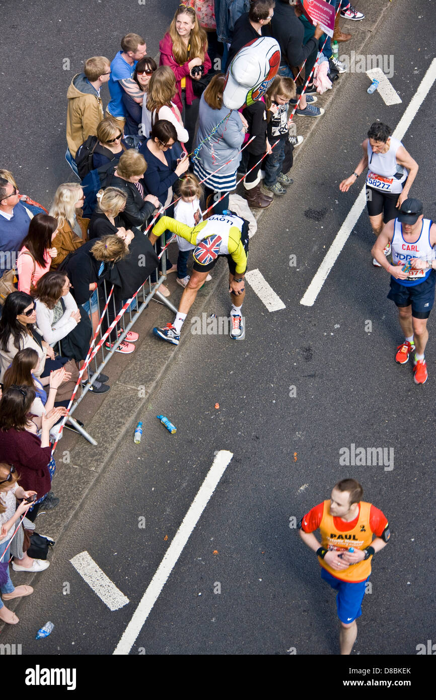Runner competitor athlete stopping to stretch legs during 2013 London marathon Victoria Embankment England Europe - Stock Image