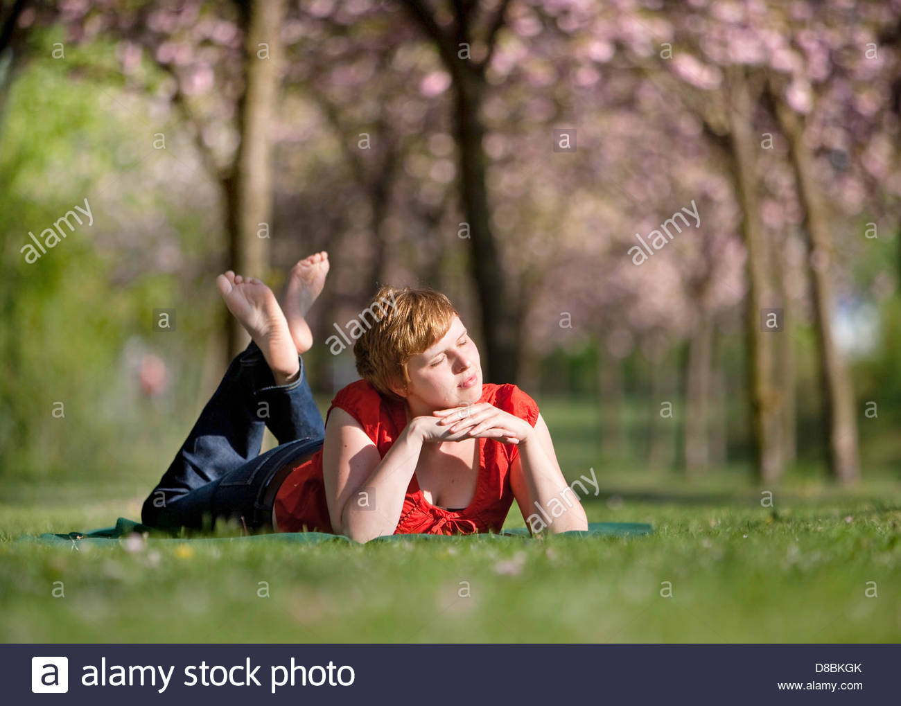 Young woman taking sun bath in a garden and day dreaming, Berlin, Germany Stock Photo