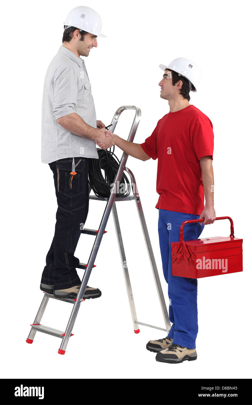 Two workers greeting each other with a hand-shake - Stock Image