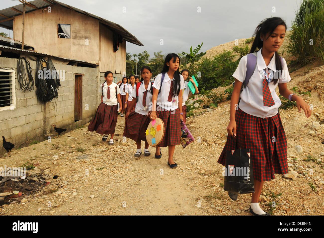 Filipino schoolchildren walk along the street in the coastal town of Puerto Galera. Mindoro Island, Philippines - Stock Image