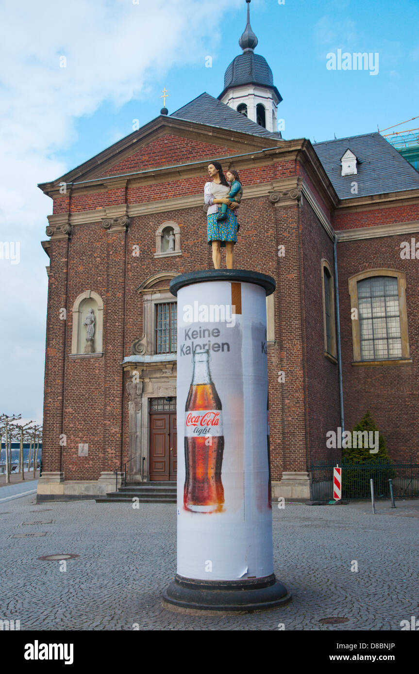 Mother and child pillar with coca cola advertising in front of Basilika St Lambertus church Altstadt old town Dusseldorf - Stock Image