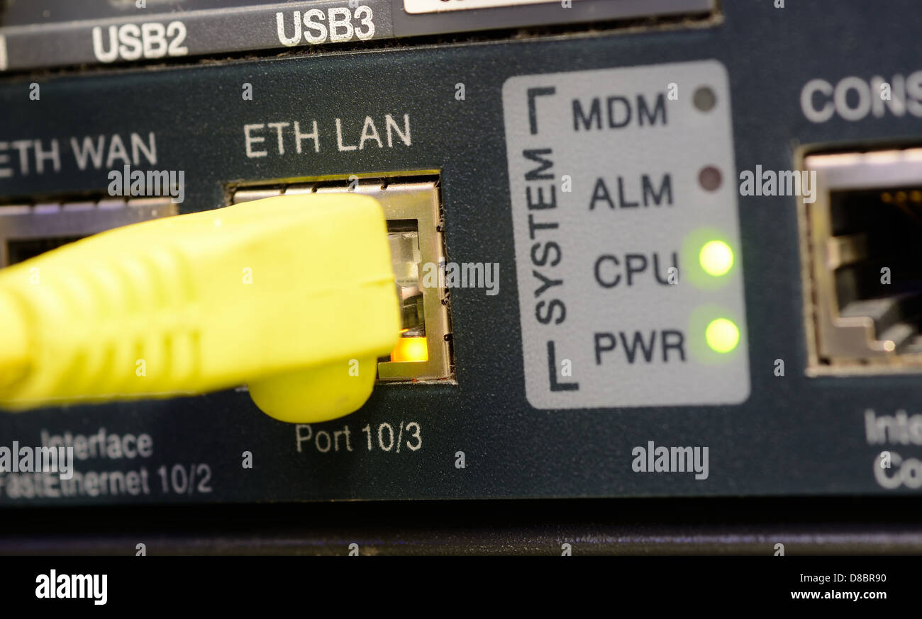 Yellow patch cord plugged to the ethernet port. - Stock Image