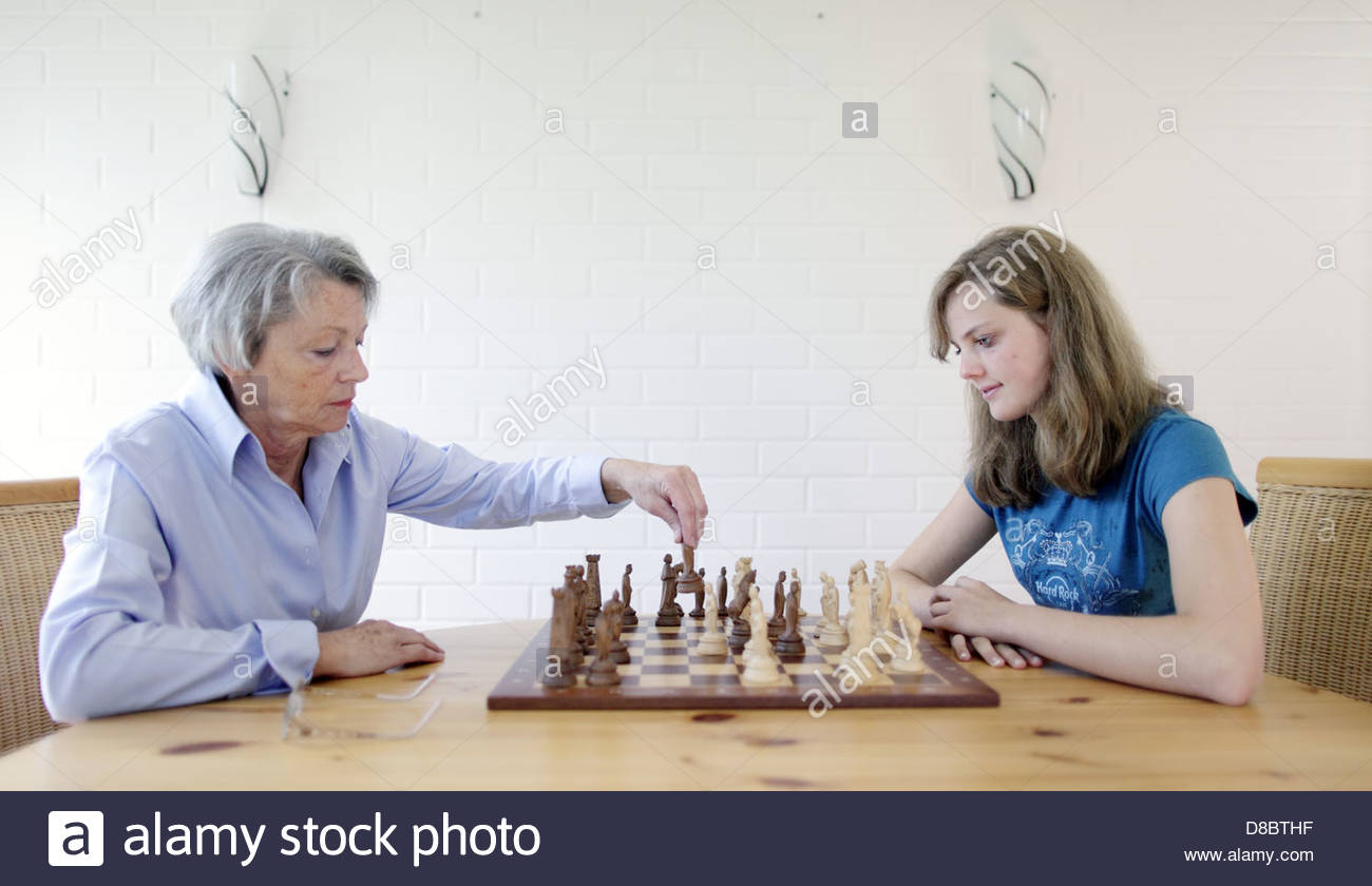 Granddaughter and grandmother playing chess - Stock Image