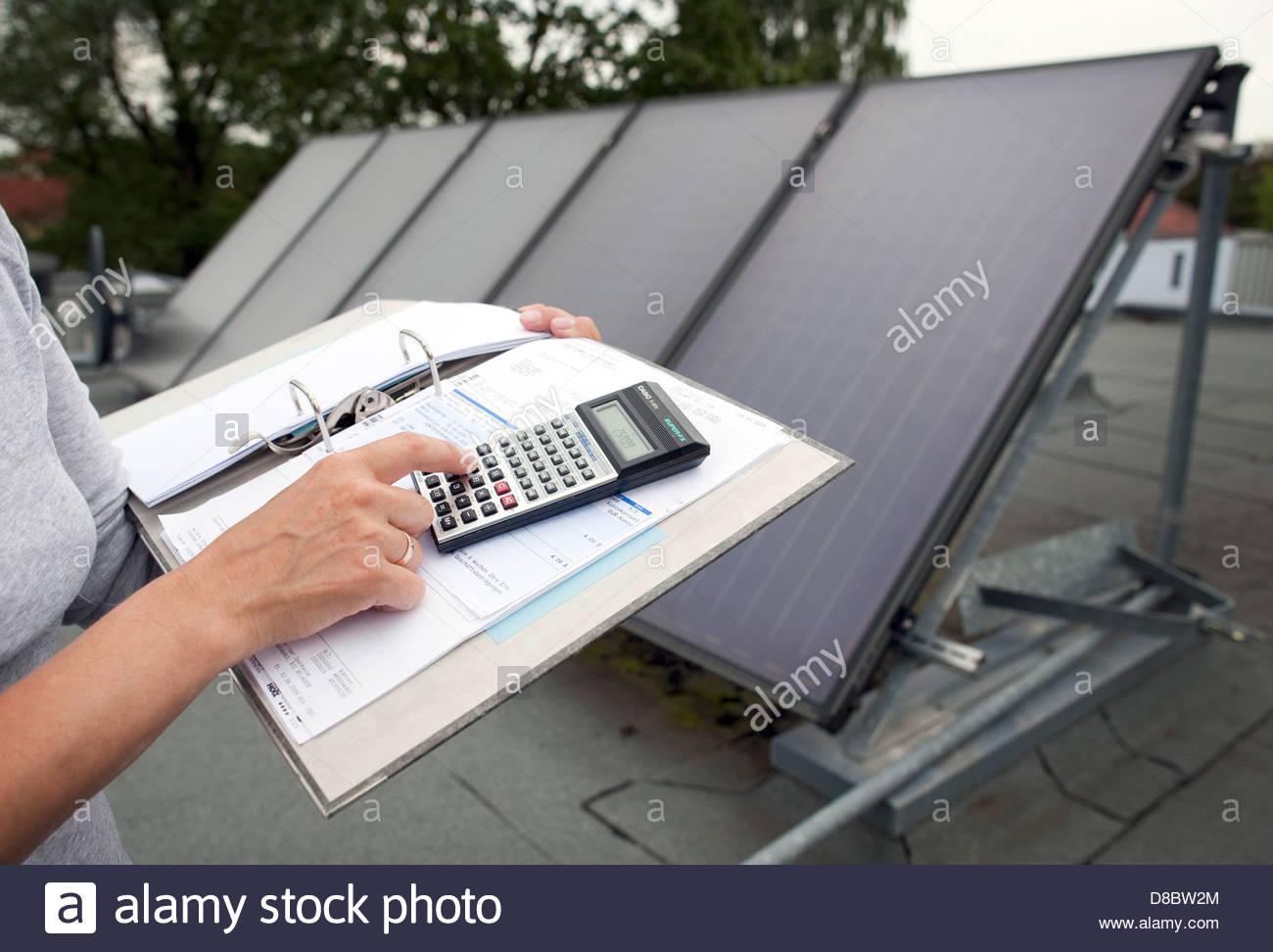 Technician holding a calculator near solar panels - Stock Image