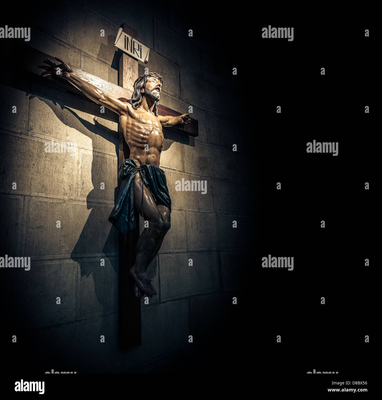 Crucifix on wall in spotlight inside old dark church or cathedral. Jesus Christ on cross. Religion, belief and hope. - Stock Image