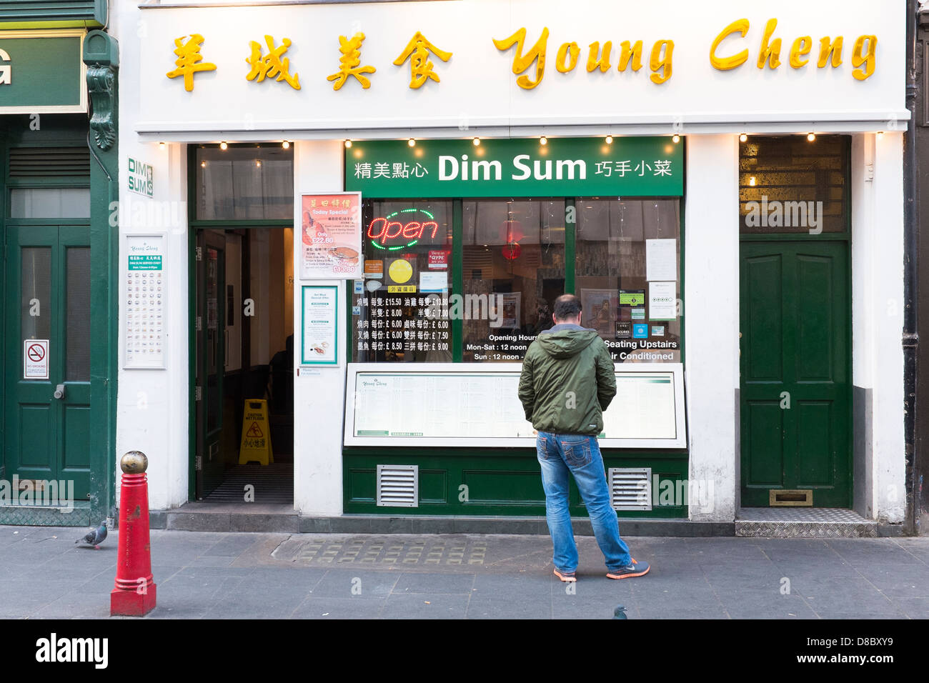 Man outside Chinese restaurant in china town london - Stock Image