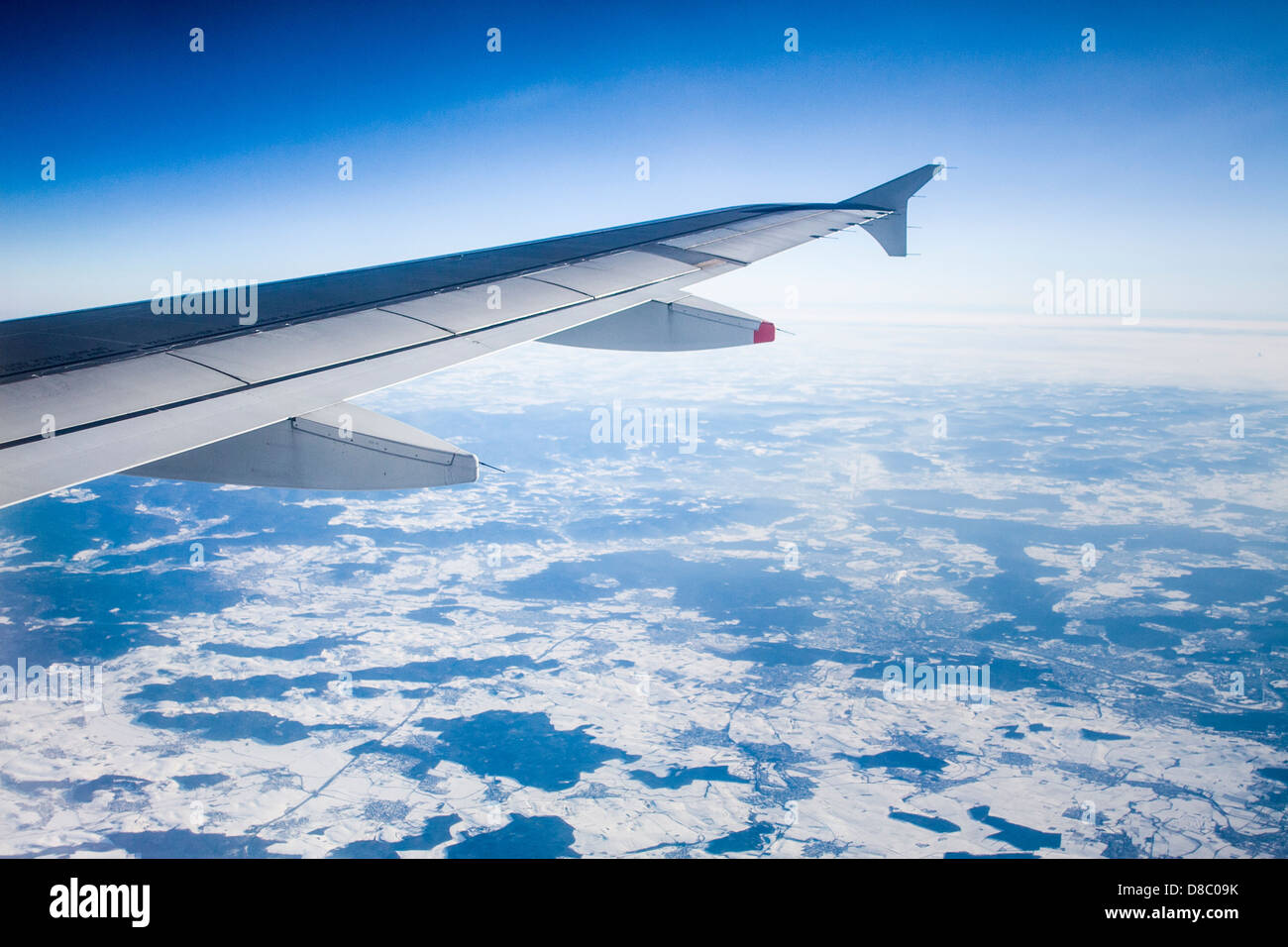 Airplane wing over a snowy land. - Stock Image