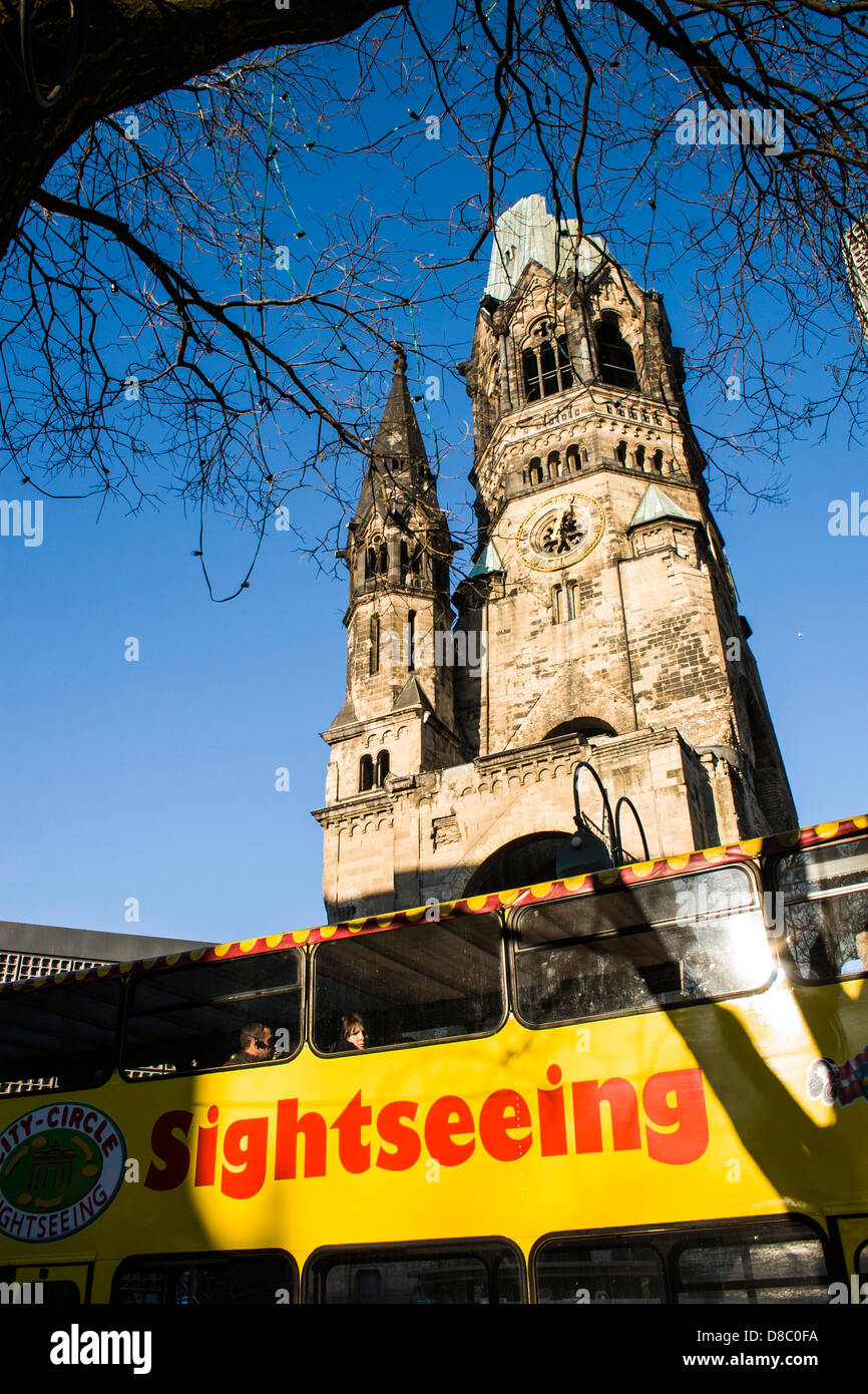 Kaiser Wilhelm Memorial Church (Kaiser Wilhelm Gedächtniskirche) and a sightseeing bus. - Stock Image