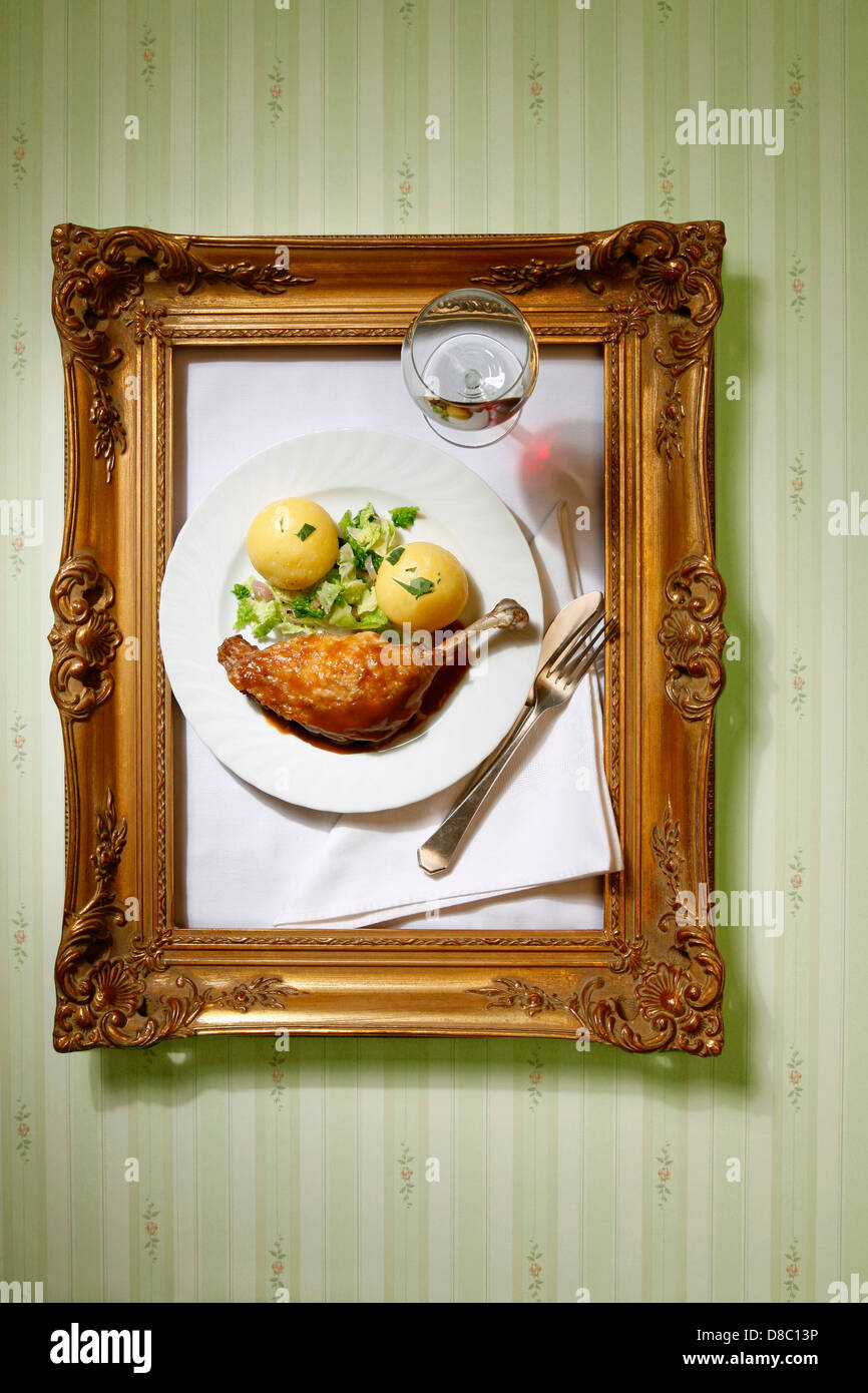 Plate with canard joint and dumping hanging in golden frame at the wall - Stock Image