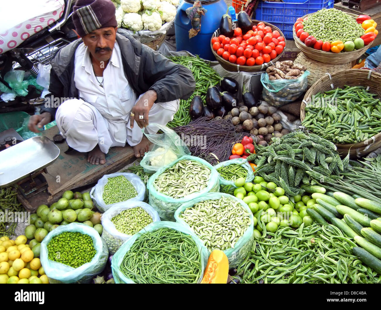 Indian street vendor selling selling fresh vegetables and fruits in farmer's market , Ahmedabad, India - Stock Image