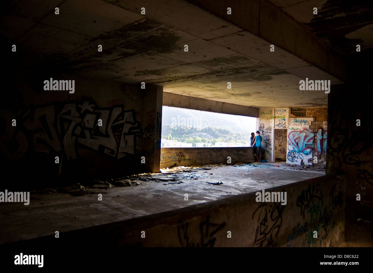 Young couple in graffitied and derelict Stara Banka Staklena building in Mostar in Bosnia Herzegovina Stock Photo