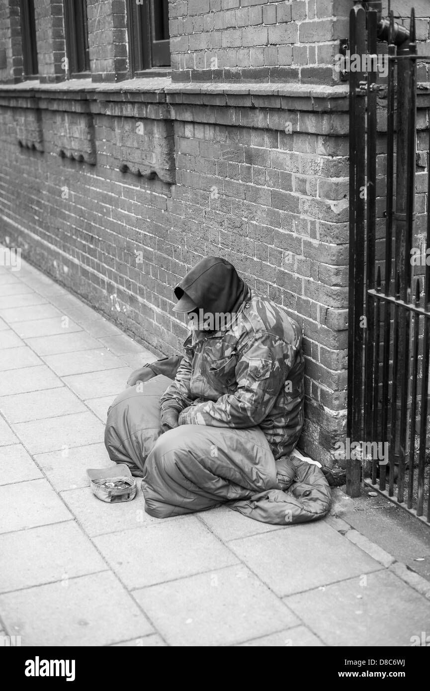 Homeless man sitting down begging for money on the streets of salisbury stock image