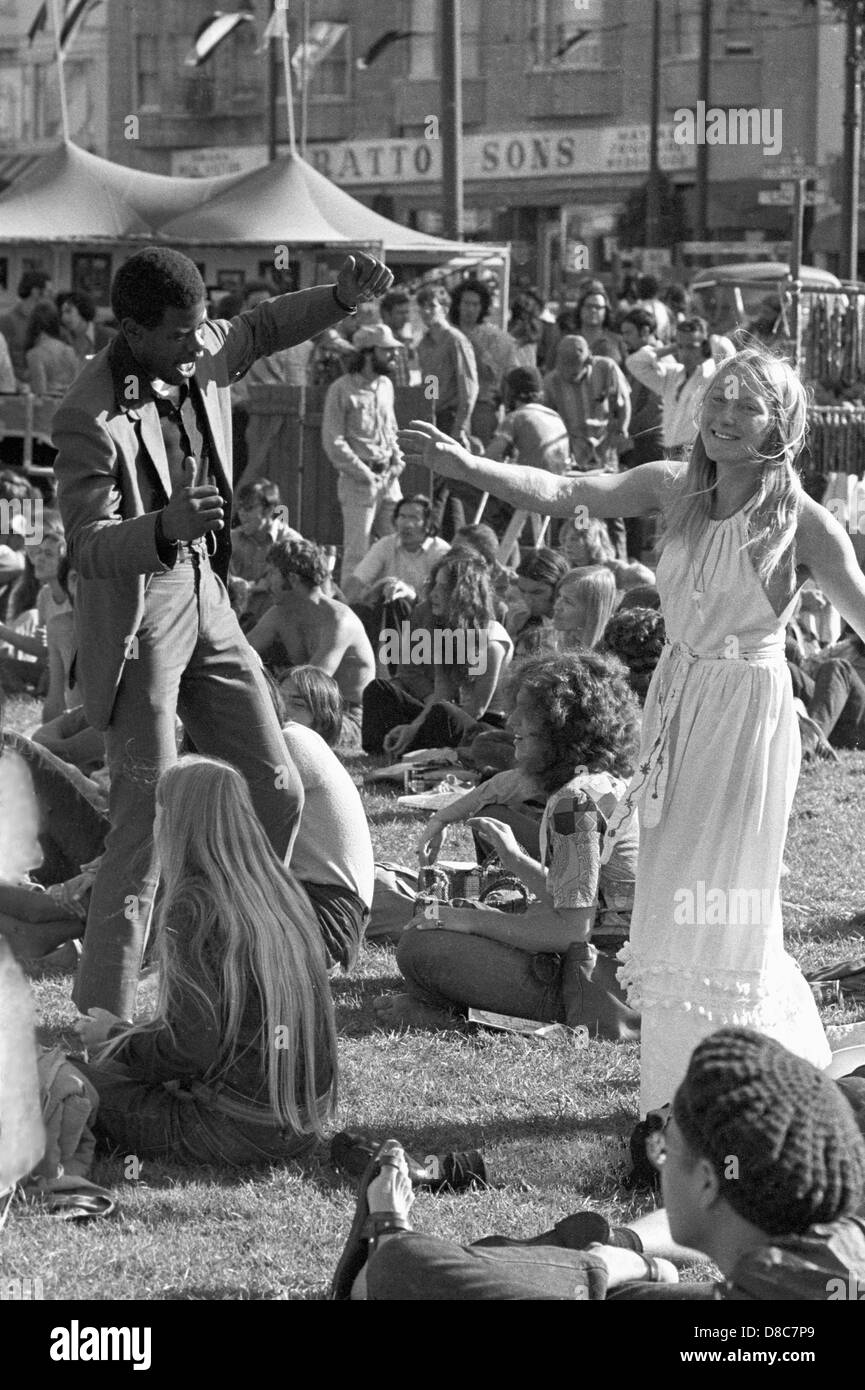 black man and hippie woman  dance at music festival in sixties - Stock Image