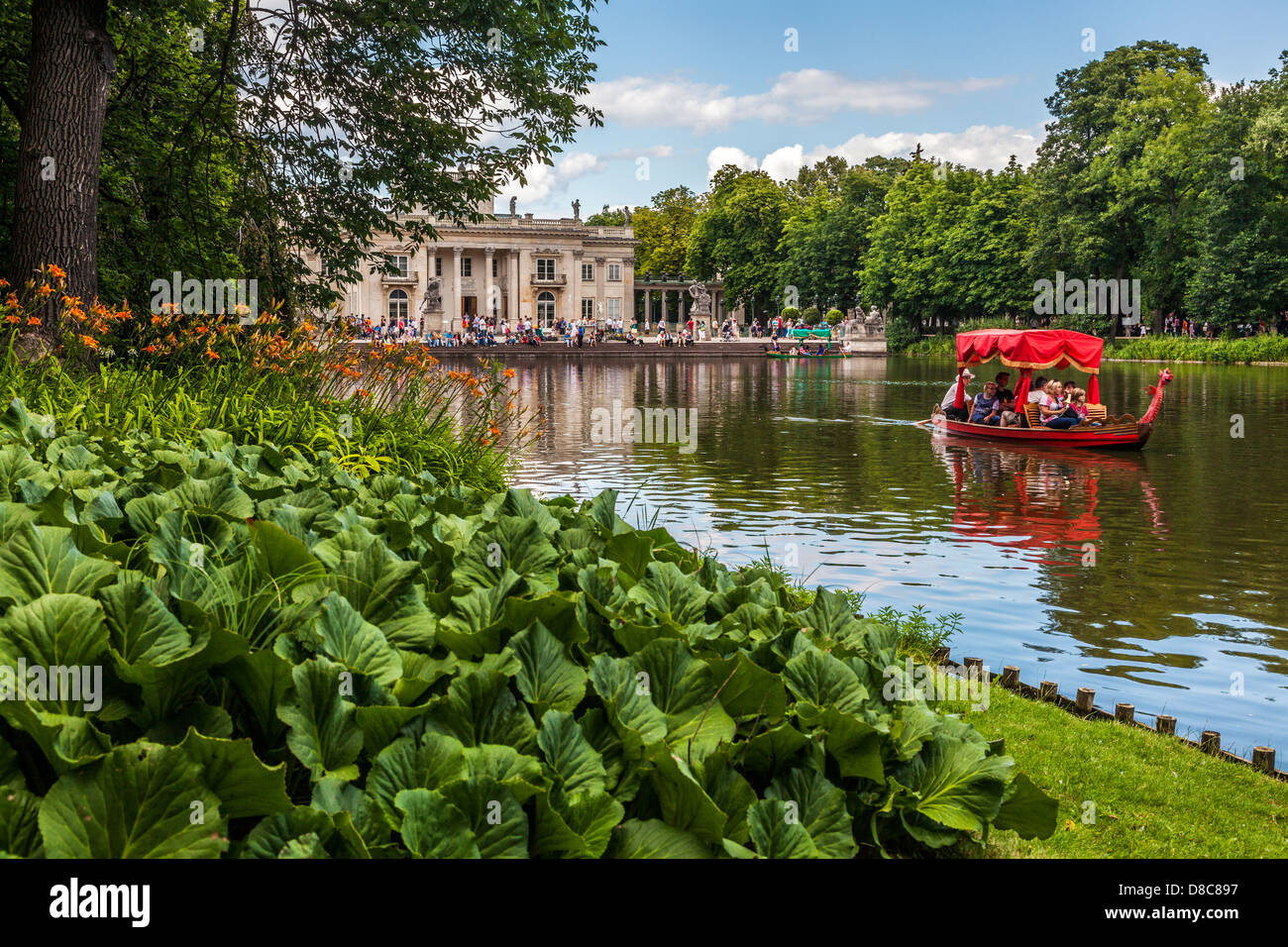 Tourists enjoy a gondola trip on the lake in Łazienki Park Łazienkowski, largest in Warsaw with the Palace in the - Stock Image
