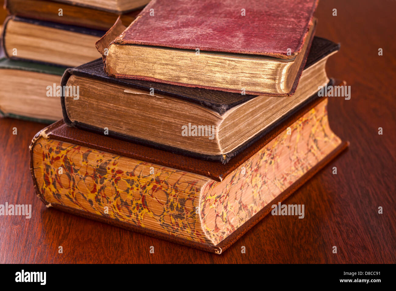 Old Books on Dark Wood Background - battered old books on a dark oak table, focus on foreground. - Stock Image