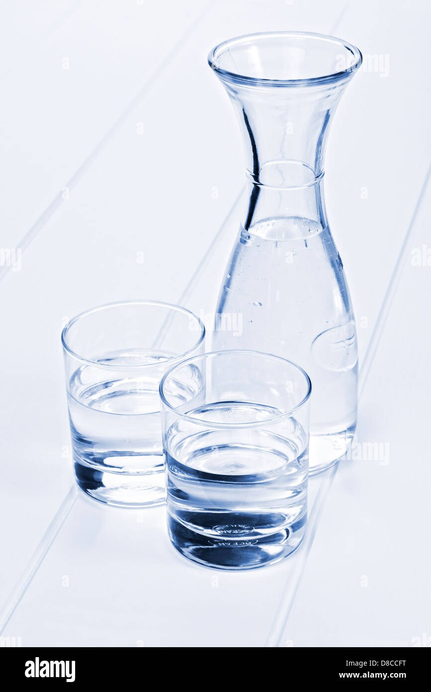 Water Carafe and Two Glasses - a carafe of water on a table with two glasses, blue toned. - Stock Image