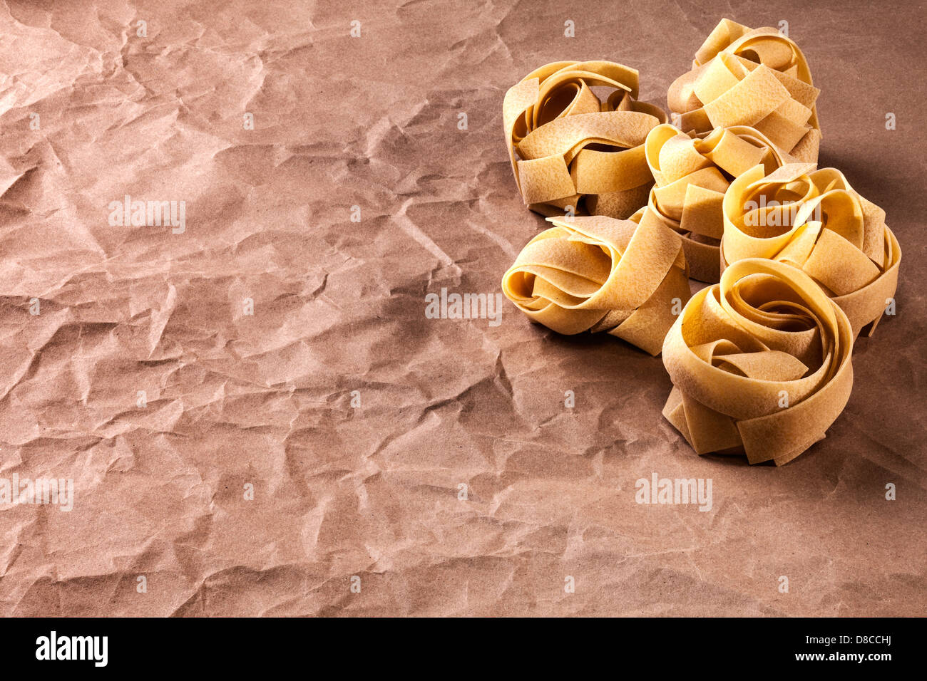 Fettucine Pasta on Brown Paper Background - fettucine or tagliatelle or pappardelle pasta on a background of crumpled... - Stock Image