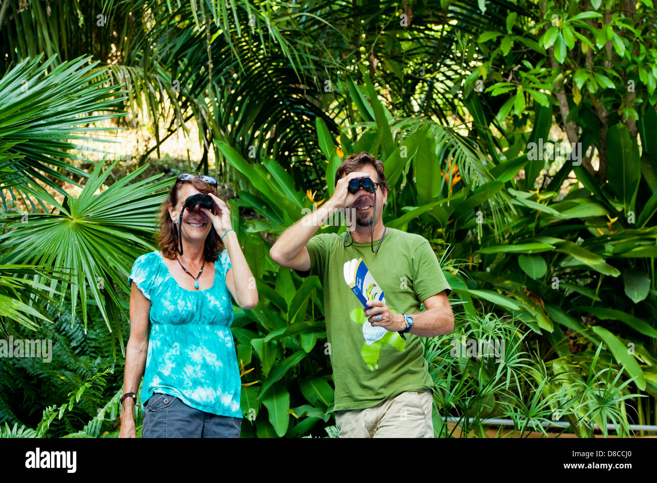 Man and woman bird watching in jungle Stock Photo