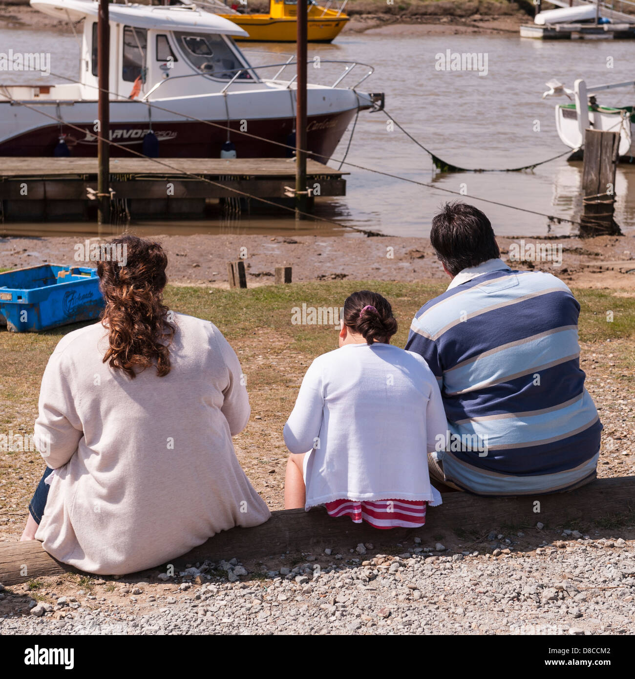 A rear view of 3 large people eating fish and chips at the harbour in Southwold , Suffolk , England , Britain , - Stock Image