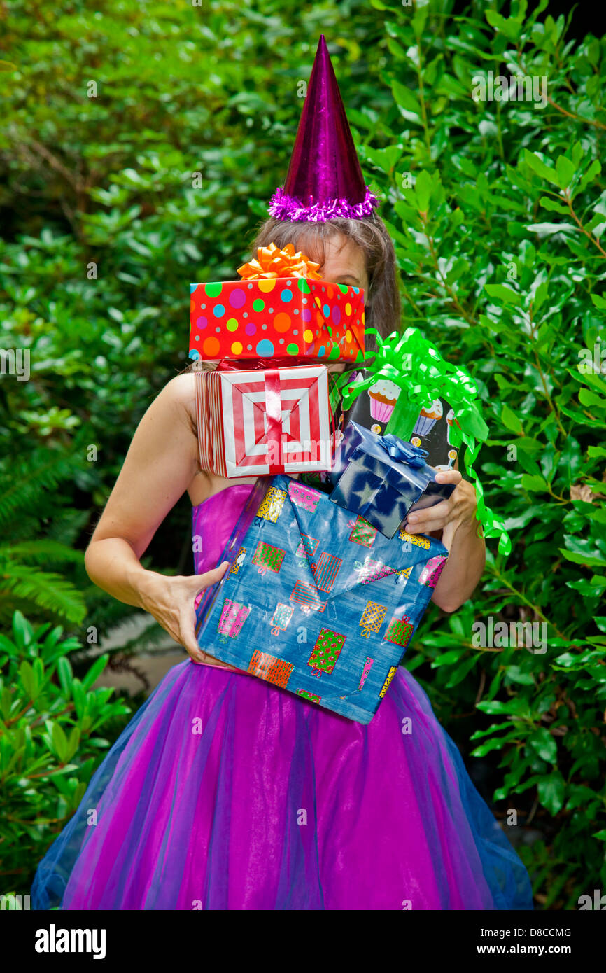 Woman in party clothes holding presents Stock Photo