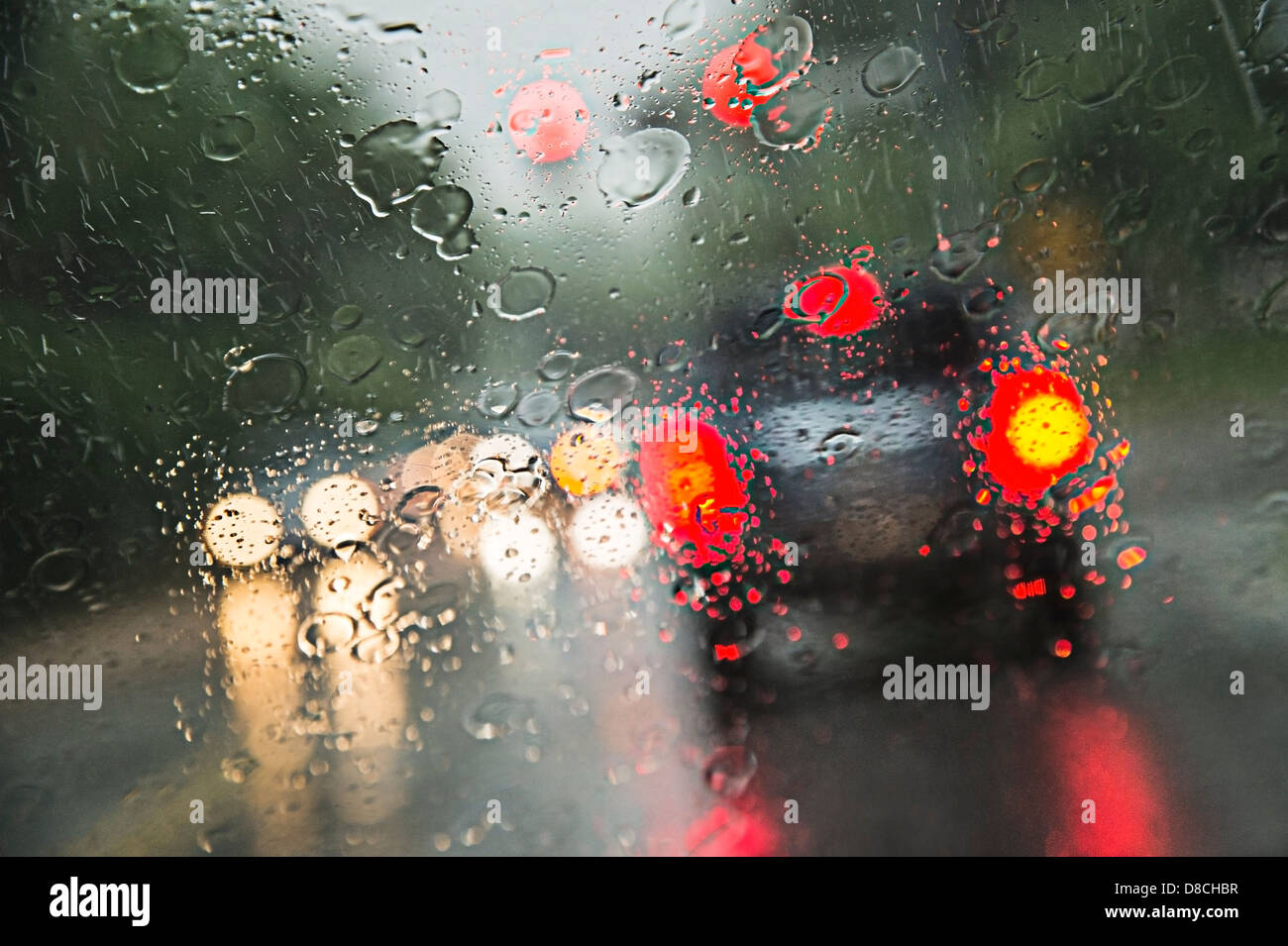 Rain On Windshield With Cars Driving In Rain Storm - Stock Image