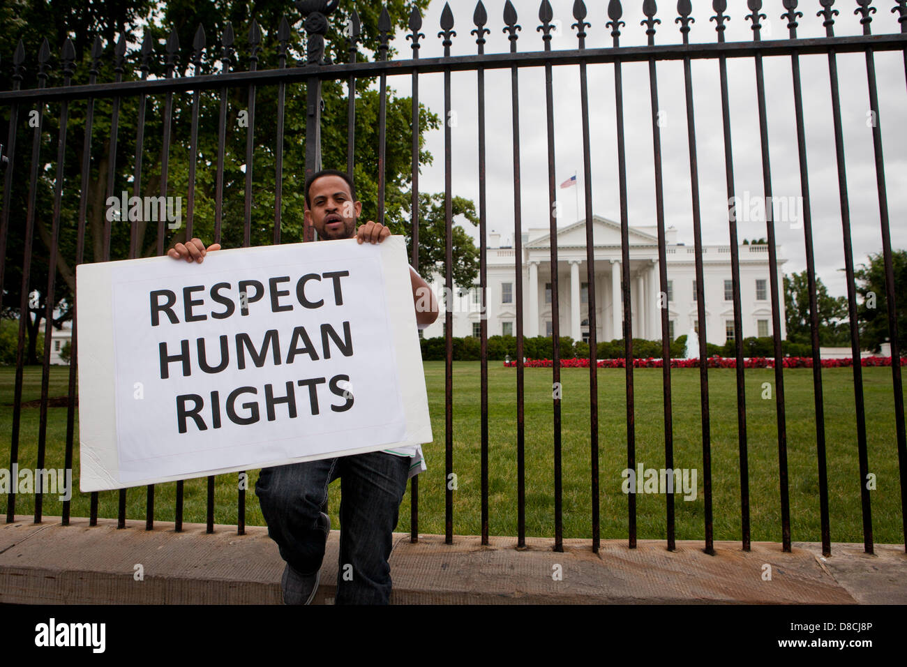 Human rights activist holding a sign outside of the White House fence - Washington, DC USA - Stock Image