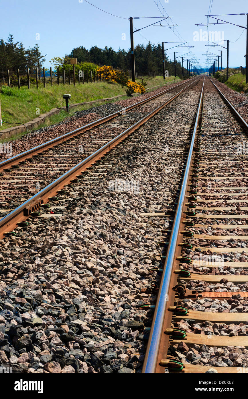 Railway tracks travelling into the distance with electric overhead cables, Scotland, UK Stock Photo