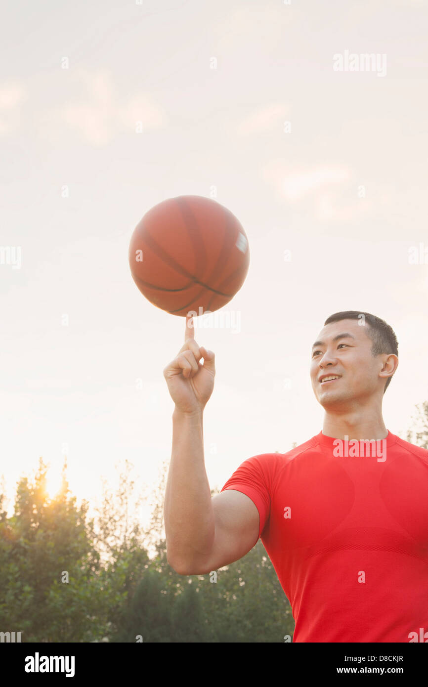Athletic Man Spinning Basketball - Stock Image