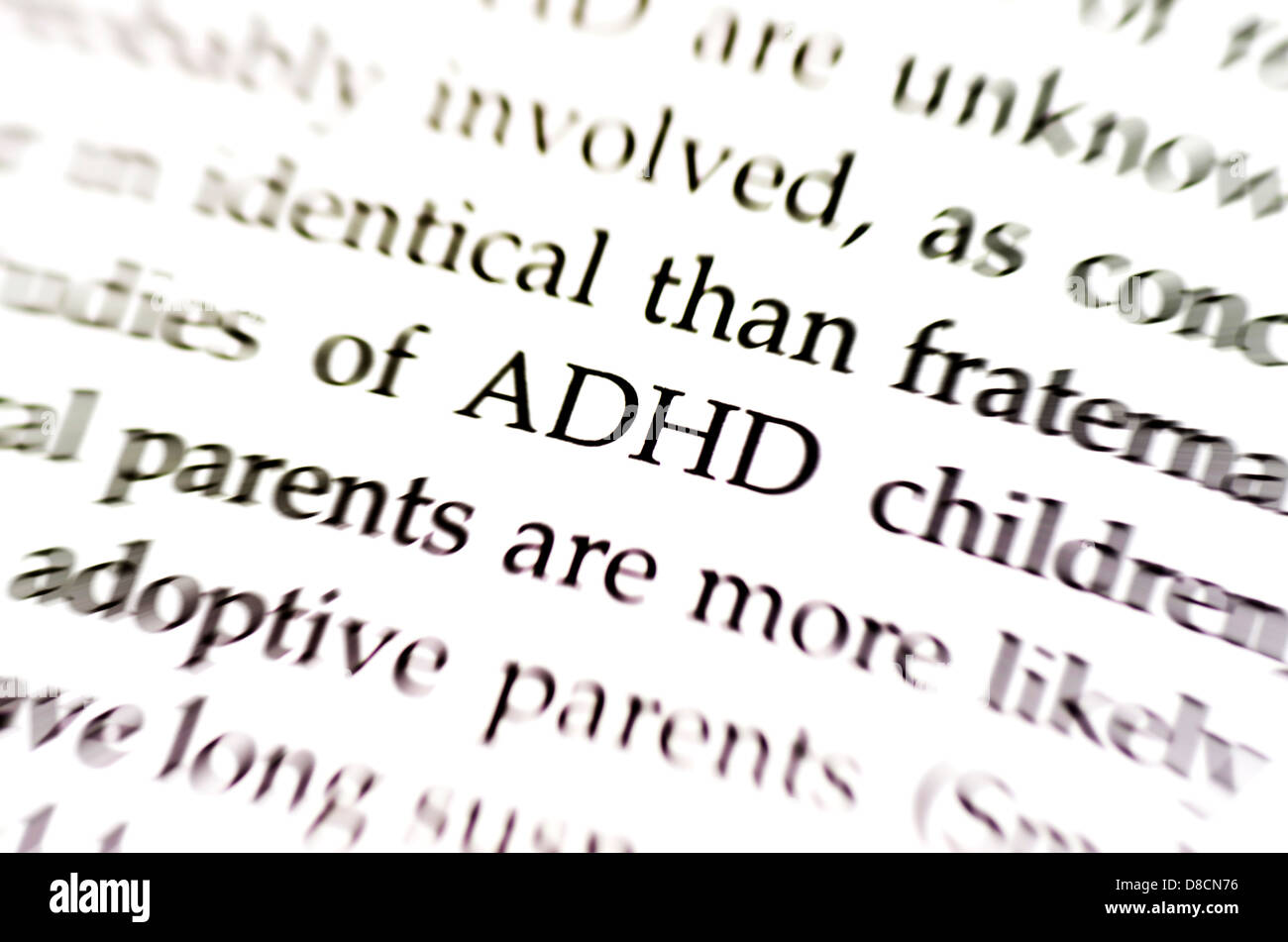 the word adhd in focus surrounded by blurred words - Stock Image