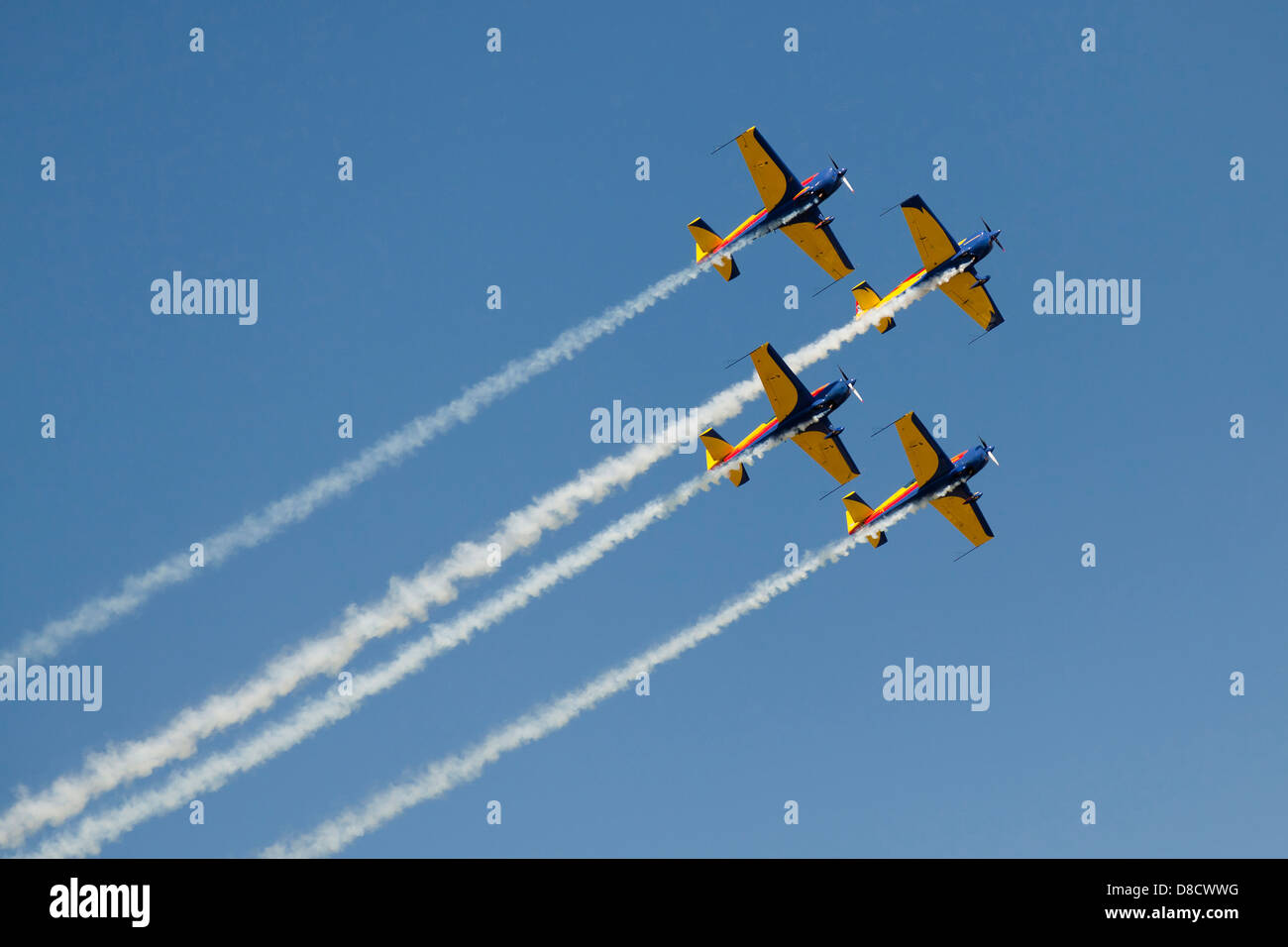airplanes on a blue background leaving a smoke trail - Stock Image