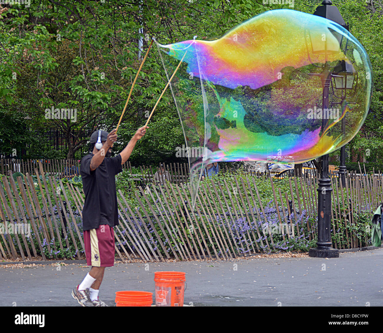 Man in Washington Square Park in New York City blowing large bubbles. - Stock Image