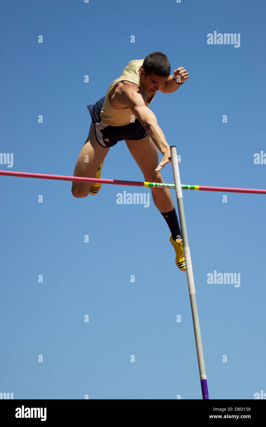 Pole Vaulter clears the bar - Stock Image