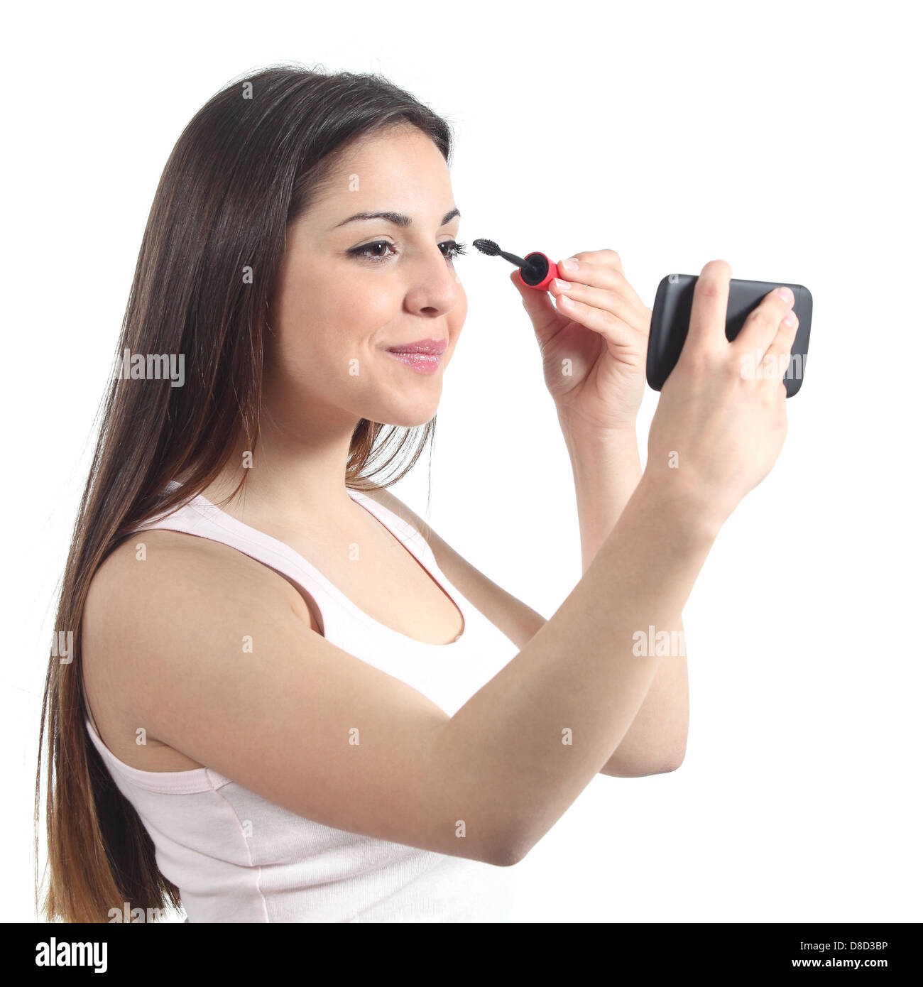 Beautiful teenager girl making up using her phone like a mirror - Stock Image